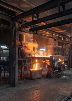 Dramatic lighting and the red glow of molten metal inside a steel factory.