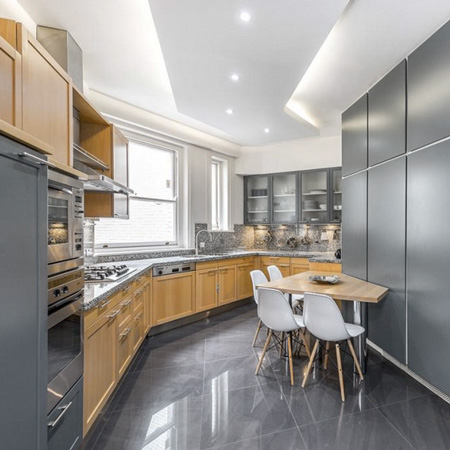 An angled kitchen with two-tone cabinets, a granite countertop, marble floors and a dropped ceiling with cove lighting.