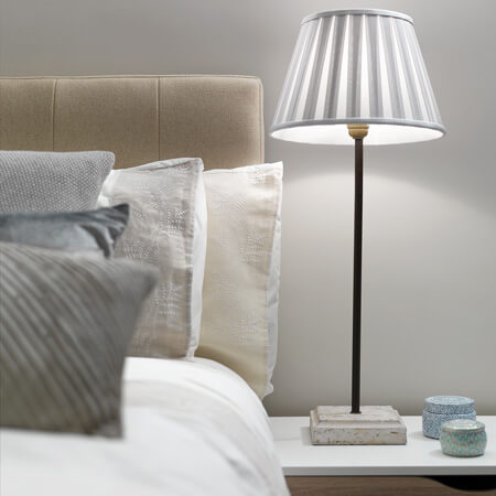 A romantic chic bed with beige luxury bedding next to a rustic bedside table with a concrete lamp and trinket boxes.