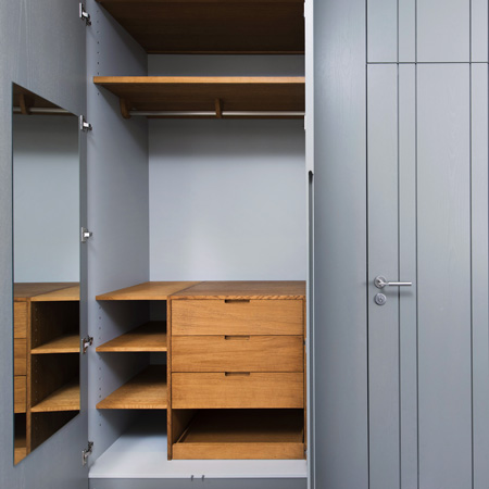 A bespoke wardrobe with natural walnut interiors and gray vertical paneling concealing a door to the ensuite bathroom.