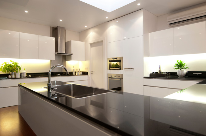 A modern black and white kitchen with white lacquered cabinets, black marble countertops and stainless-steel details.
