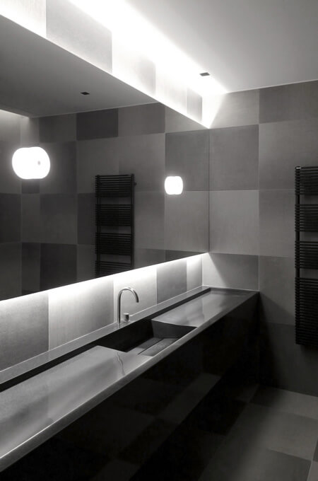A contemporary bathroom with clean lines, grey gradient tiling, a horizontal backlit mirror and a black marble vanity.