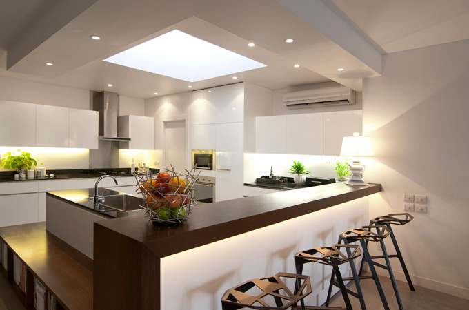 A contemporary kitchen design with a wenge wood bar counter, black Konstantin Grcic stools and a feature skylight.