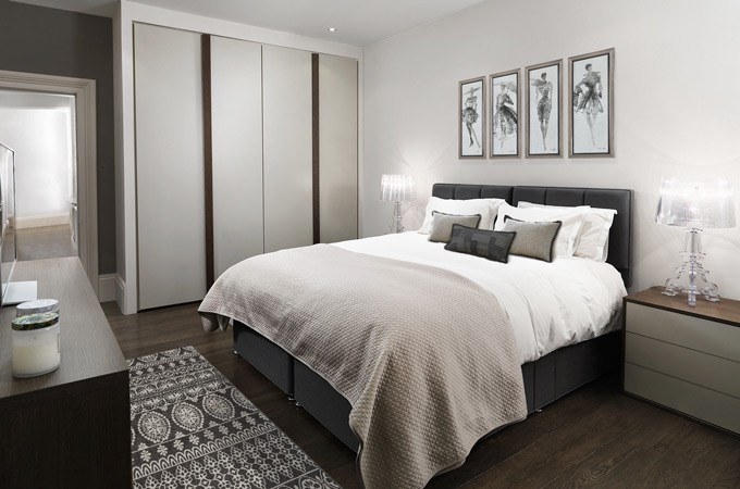 A cozy modern bedroom in shades of grey, beige and taupe with walnut floors and custom-built wardrobes.