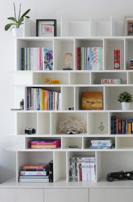 A custom-made modern white bookshelf displaying a variety of eclectic and colorful books, antiques and collectables.