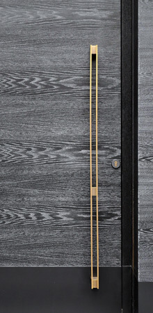 A custom-made door design using crown cut grey Zebrano wood and a minimal gold vertical pull handle.
