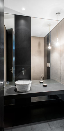A dark minimalist bathroom with black slate features, silver wallpaper and a white Carrara marble vessel sink.