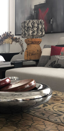 Eclectic décor featuring a Moroso sofa, an aged wooden table, modern patchwork cushions and antique accessories.