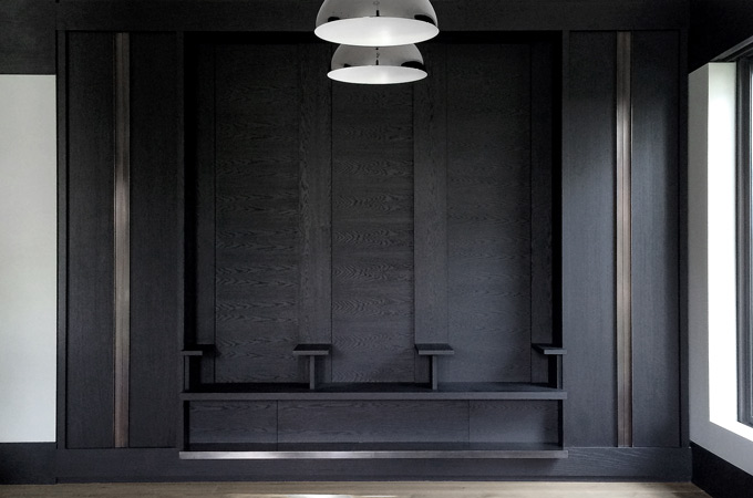 A feature wall with dark wood paneling, bronze vertical inlays and a floating bench.