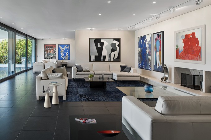 A high-end residential interior with floor-to-ceiling windows, slate floors, luxury designer furniture and modern artwork.