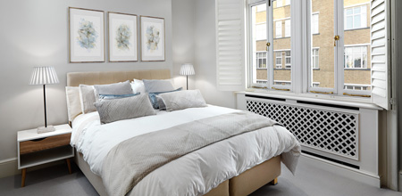 A light and airy bedroom in a soft natural color scheme with linen, cotton, silk and velvet bedding.