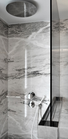 A black and white marble walk-in shower with a glass screen and a rainfall shower head.