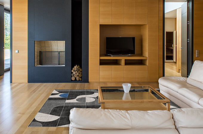 A minimalist living room with a beige leather sofa, oak wall paneling and a slate fireplace with a niche for wood logs.