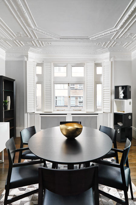 A modern classic dining room with a decorative ceiling, plantation shutters, contemporary furniture and a gold accent bowl.
