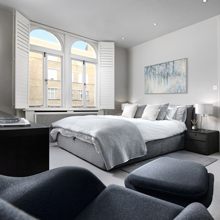 A modern classic bedroom designed in a grey color scheme with luxury bedding and a charcoal armchair with matching footstool.