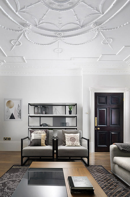 A modern classic living room featuring contemporary designer furniture and classic architectural details.