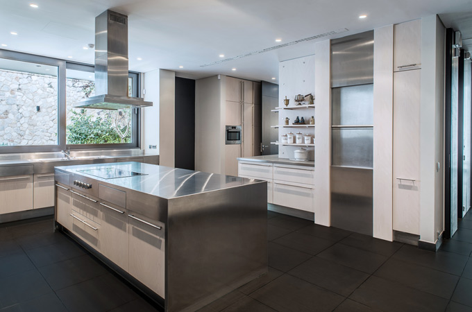 A modern minimalist kitchen design with a stainless steel island and black slate floors.