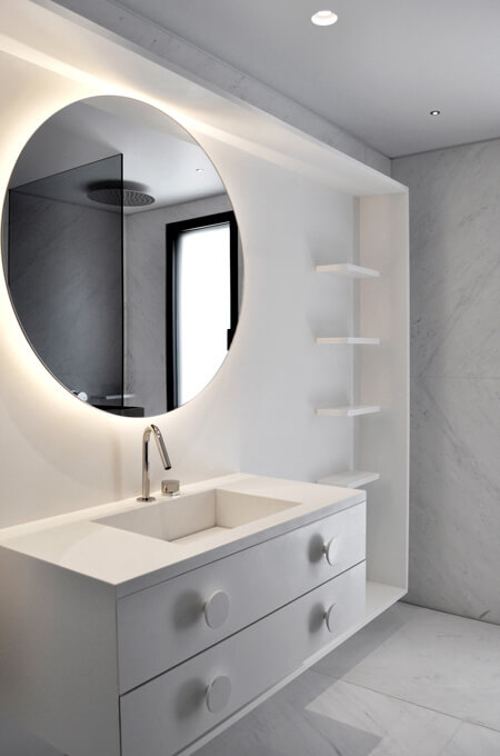 A modern bathroom vanity in a white floating fame, with a Corian sink, a round backlit mirror and circular drawer knobs.