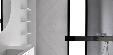 A white marble bathroom with a walk-in shower, glass screen and black chrome bathroom accessories.