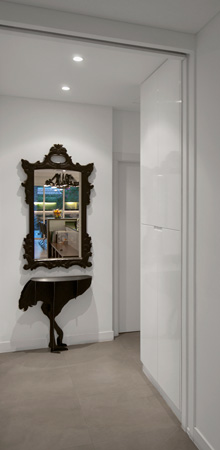 A white minimalist corridor with built-in lacquered cabinets, a feature baroque mirror and an ostrich shaped console.