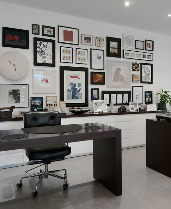 An eclectic style home office with an L-shaped wenge desk, a Herman Miller chair and picture frame feature wall.