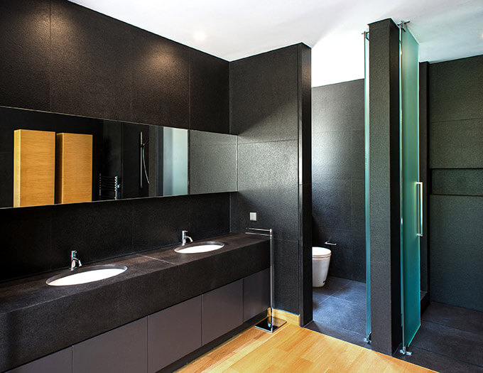 A bold black bathroom design with slate walls, oak floors and frosted glass doors.