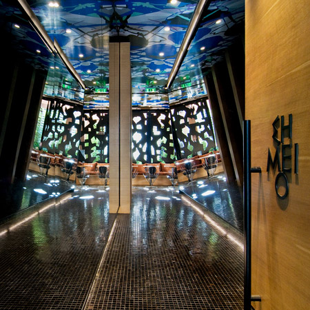 A bar entrance with angled mirror walls creating a kaleidoscopic illusion.