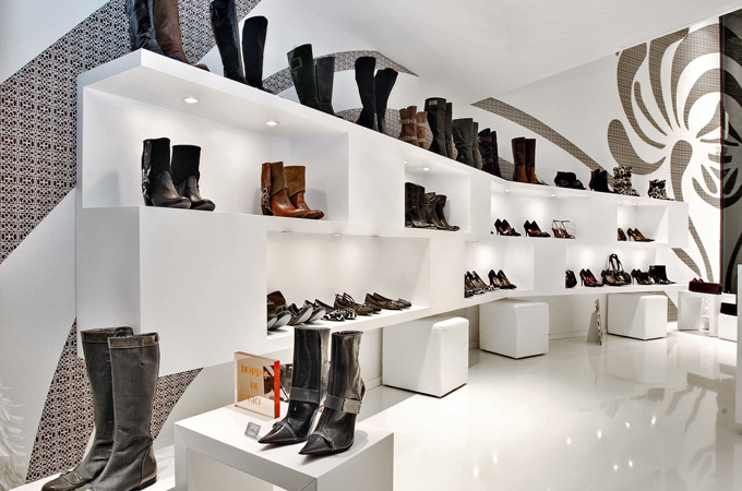 A two-tone contemporary retail store design with white display stands and a brown floral wall pattern.