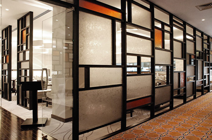 A custom partition screen made of a geometrical wooden grid with frosted and orange glass panels.