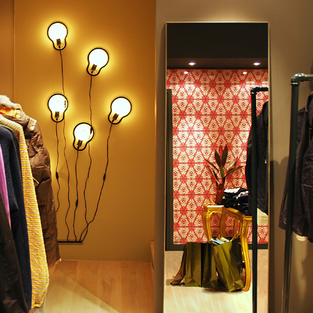 The interior of a modern retail shop with a red fractal feature wall and playful lighting.