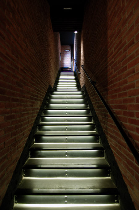 An industrial style commercial staircase with brick walls and underlit steps made of concrete and metal.