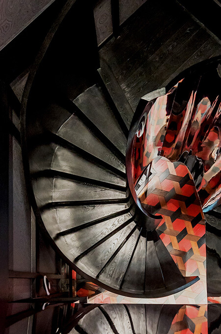 A contemporary black spiral staircase with a reflective balustrade leading to a red and black patterned floor.