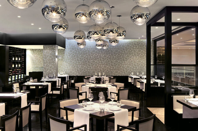 A restaurant design for the Intercontinental Hotel with dark furniture, blue grey wallpaper and Tom Dixon lights.