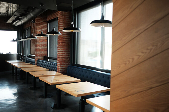 An urban rustic restaurant design with wooden tables, brick walls and polished concrete floors.