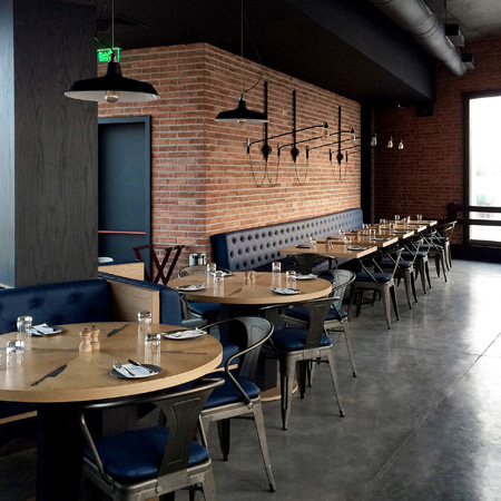 A warehouse chic restaurant interior with brick walls, industrial lighting and leather booth seating.