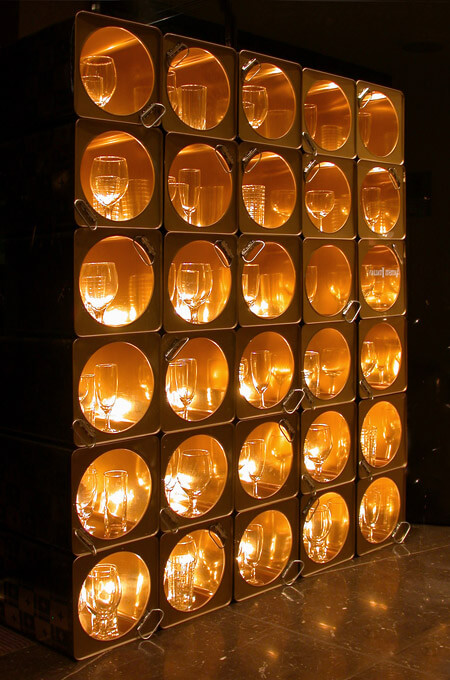 A feature partition wall made from oil tin containers with internal lighting that creates a golden glow.
