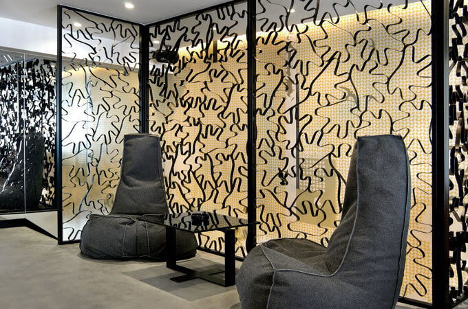 A contemporary restaurant lounge area with beanbag armchairs and metal partition screens.