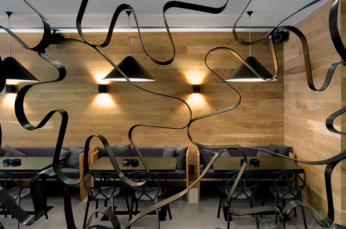 An urban cafe restaurant interior with natural wood walls, Tom Dixon cone lights and black furniture.