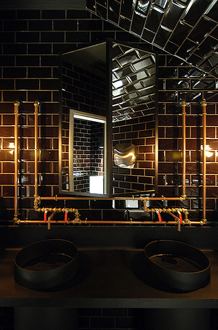 An industrial style commercial restroom with black metal wash basins and exposed copper pipework.