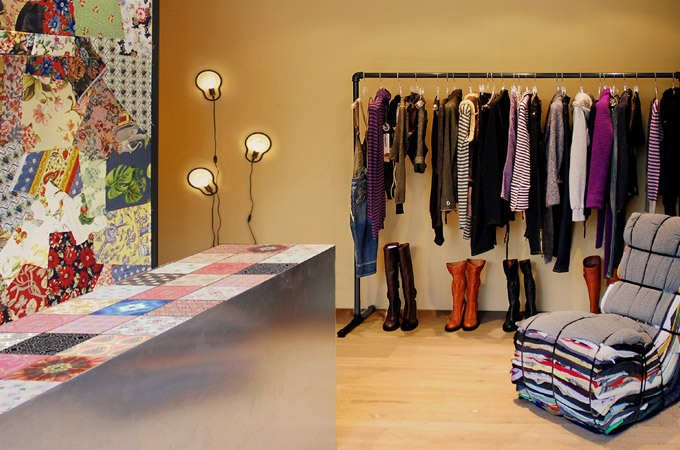 An eclectic style boutique interior using patchwork wallcoverings, colorful tiles, galvanized steel and distressed oak.