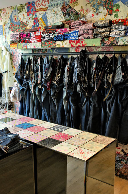 An eccentric retail interior with patchwork walls, multi-color tiles and steel pipe railing displaying jeans.