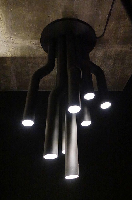 Custom-made lighting using black metal pipes in an industrial style restaurant.