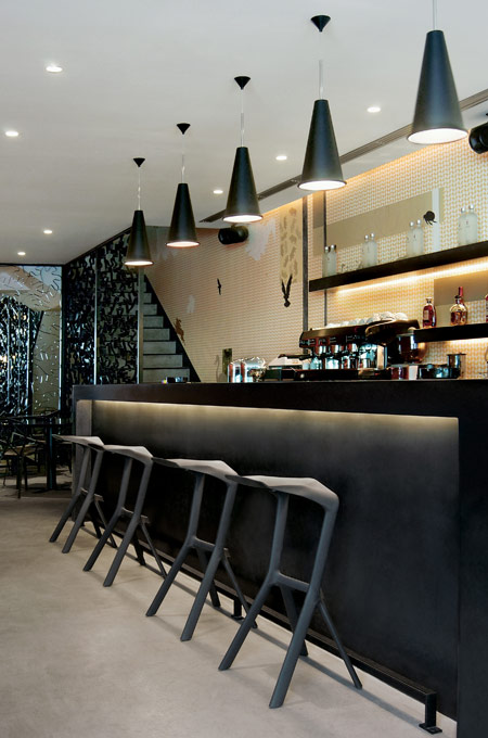 An elegant black bar design with conical pendant lights and polymorphic bar stools.