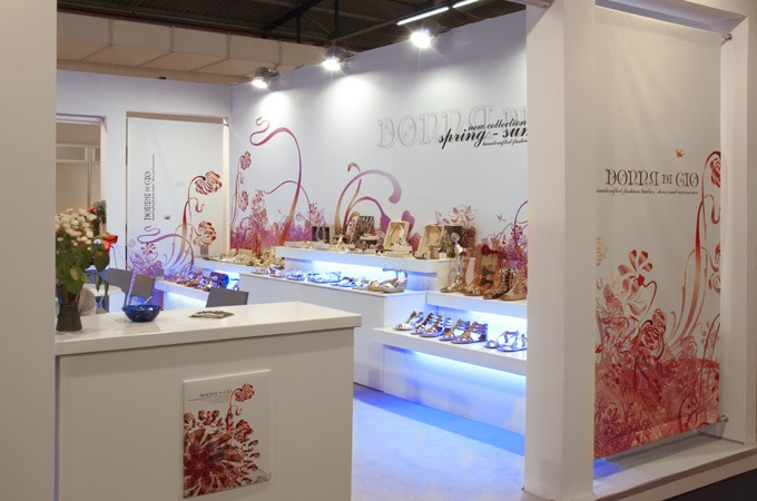 An airy exhibition booth designed with floating underlit shelves and floral graphics.