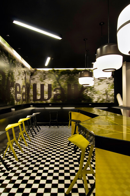 A modern cafe bar interior with polygonal forms, black and white checkered floor, and bold yellow accents.