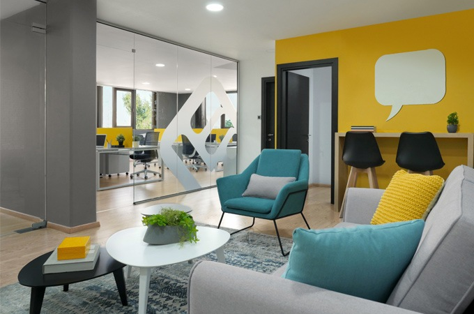 A creative workspace design for a tech startup with bright colors, graphics and contemporary furniture.