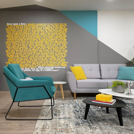 A modern colorful office lounge with a painted wall design and motivation quote.