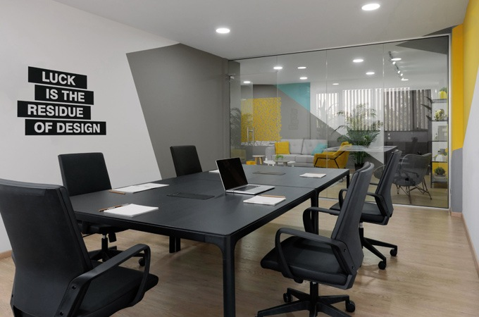 The modern office design of a meeting room with black furniture looking out onto a colorful common area.