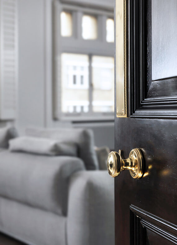A French polished door in a dark finish, with a gold knob and plate, leading into a light and airy living area.