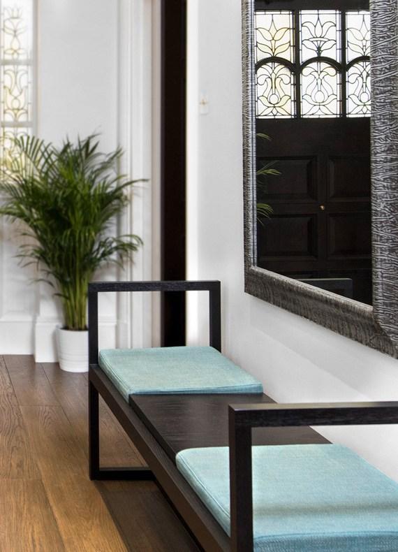 A minimalist wenge bench under a silver framed wall mirror.